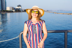 Summer holidays, vacation, travel and people concept - smiling young woman wearing sunglasses and hat on beach over sea. Summer holidays, vacation, travel and Royalty Free Stock Image