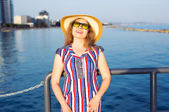 Summer holidays, vacation, travel and people concept - smiling young woman wearing sunglasses and hat on beach over sea Royalty Free Stock Image