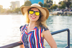 Summer holidays, vacation, travel and people concept - smiling young woman wearing sunglasses and hat on beach over sea. Summer holidays, vacation, travel and Stock Image