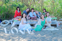 Summer holidays and vacation - young womens eating and drinking on the beach stock photo