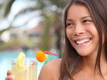 Summer holidays woman. Drinking alcoholic drink outside by the pool at a tropical resort royalty free stock photos
