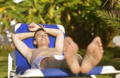 Summer holidays. Young man sunbathing. In the background a palm tree. Vacation concept. Man freelancer lies on a blue lounger. Sun shine. First minute Stock Photo