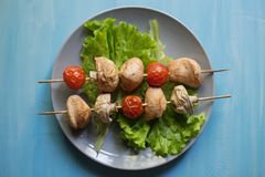 Summer homemade skewers on wooden skewers: chicken fillet, mushrooms and cherry tomatoes in a plate with lettuce on a blue table royalty free stock photography
