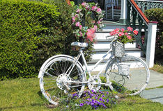Summer homes in Jersey shore. Decorative white painted bicycle stands on the lawn in front of the house near the stairs, hedges and flower beds. Jersey shore US royalty free stock image