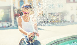 Summer hot day. Cute little girl playing with fountain. Hot weather Stock Photos