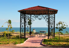 Summer-house with bench and sea on background. Summer-house with two benches and table, tiled path and sea on background stock image
