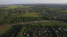 Summer houses in the countryside and freight train, aerial view. Aerial panorama of countryside with summer houses among green woods and moving cargo train stock video