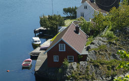Summer-houses in Norway. Summer-houses and two small boats at the Norwegian south coast near Farsund Royalty Free Stock Image
