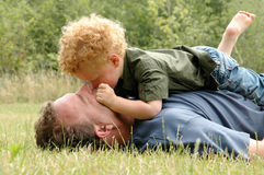 Summer Hugging. Father and son cuddling on grass Royalty Free Stock Photos