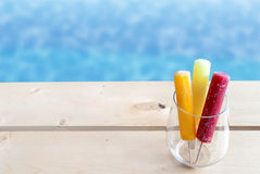 Summer ice lollies. Frozen ice lollies in a glass by a swimming pool Stock Photo