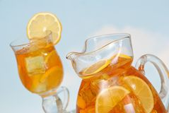 Summer Iced Tea. Jug and glass of iced tea in summer - focus on glass jug royalty free stock photos