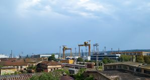 Summer industrial landscape: blue sky, railway with trains and freestanding wagons, loading cranes, old and new industrial buildin. Gs, some of which are royalty free stock images