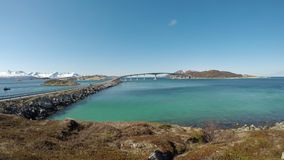 The summer island bridge in northern norway on a clear blue spring day. With calm moving waves and strong sunshine stock video footage