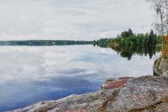 Summer, island on the lake in park Monrepo. In the natural park `Monrepo` in the city of Vyborg there is a lake. There is an island overgrown with trees. The Royalty Free Stock Image