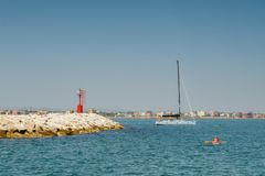 Rocky shore, blue sea, a man in a kayak, a white yacht with passengers, a clear blue sky stock photography