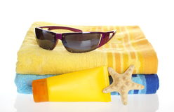 Summer item. Sunglasses, sun lotion and towel on white background stock photography