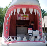 Summer Jobs. Bored teenager selling lemonade out of a giant great white shark head at a New England amusement park stock photos
