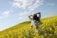 Summer joy. Girl in jeans posing in a rapeseed field stock images