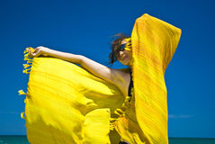 Summer jubilation. Vaporously wrapped gilr in colourful scarf, laughing and jubilating in the summer sun royalty free stock images