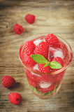 Summer juice with fresh raspberries mint and ice in a glass. On a dark wood background. toning. selective focus on mint in the glass Stock Photo