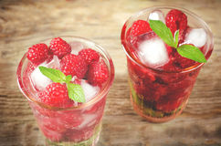 Summer juice with fresh raspberries mint and ice in a glass Stock Images