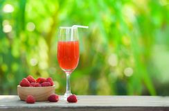 Summer juice glass raspberry cocktail and fresh raspberries fruit on wooden bowl stock photography