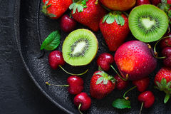 Summer juicy ripe Strawberry, cherry, kiwi and peaches On a black plate closeup. royalty free stock images