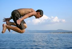 Summer jump. Teenager boy jumping into water in summer Royalty Free Stock Photo