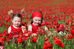 Summer kids. Happy summer kids or children sitting in fiels of poppies Royalty Free Stock Photo