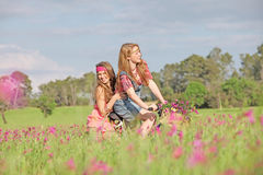 Summer kids on bike. Summer girls riding bike in field Stock Image
