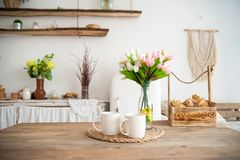 Summer kitchen interior in rustic style. Bright kitchen with a wooden table. Spring flowers and bread in a basket on the table in stock image