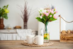 Summer kitchen interior in rustic style. Bright kitchen with a wooden table. Spring flowers and bread in a basket on the table in royalty free stock photos