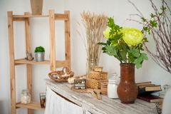 Summer kitchen interior in rustic style. Bright kitchen with a wooden table. Spring flowers and bread in a basket on the table in royalty free stock image