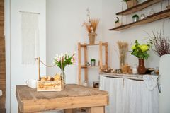 Summer kitchen interior in rustic style. Bright kitchen with a wooden table. Spring flowers and bread in a basket on the table in stock photography