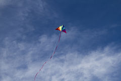 Summer, Kite of rainbow colors on a blue sky with light white cl Royalty Free Stock Images