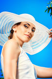 Summer lady. Portrait of a beautiful smiling woman in light white dress and elegant hat over blue sky. Beauty, fashion. Summer vacation Stock Image