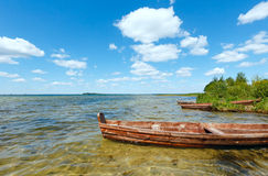 Summer lake view with wooden boats. Royalty Free Stock Image
