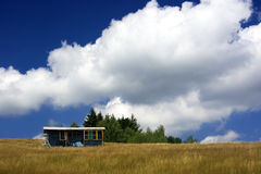 Summer landscape. Fluffy clouds and shack on field stock photo