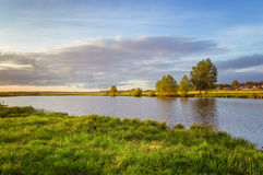 Summer landscape on the banks of the green river at sunset, Russia, Royalty Free Stock Photo