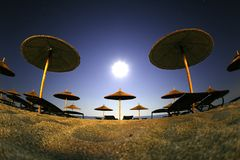 Summer landscape of beach resort with sand and straw umbrellas. Under sun light stock images