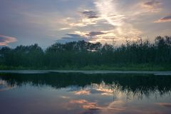 Summer landscape with a beautiful sky, which is reflected in the mirror water on the river. royalty free stock photography