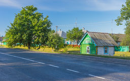 Summer landscape with big pear-tree and draw-well as a small wooden house. At roadside in Lyubka village, Sumskaya oblast, Ukraine royalty free stock image