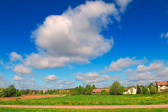 Summer landscape of blue sky, white clouds and green field. Summer landscape with the blue sky, white clouds and green field stock photo