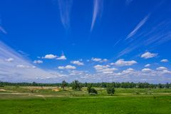 Summer landscape blue sky with white wispy clouds royalty free stock photo
