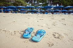 The blue slippers on the beach with white sand, against the backdrop of sun loungers with umbrellas. Summer landscape. The blue slippers on the beach with white Royalty Free Stock Image