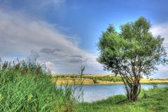 Summer landscape in Bulgarian countryside. Summer landscape with a picturesque lake and fluffy clouds somewhere in Bulgarian countryside Royalty Free Stock Photo