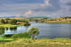 Summer landscape in Bulgarian countryside. Summer landscape with a picturesque lake and fluffy clouds somewhere in Bulgarian countryside Royalty Free Stock Image