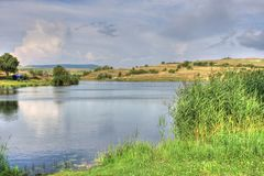 Summer landscape in Bulgarian countryside. Summer landscape with a picturesque lake and fluffy clouds somewhere in Bulgarian countryside Stock Image