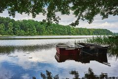 Summer landscape with calm lake and moored fishing boats under trees on the shore Royalty Free Stock Photos