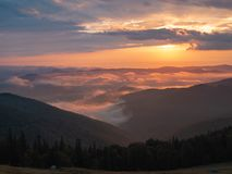 Summer landscape of Carpathians mountains, west Ukraine. Ukrainian sunset in mountains. Low orange clouds between high. Peaks illuminated by the sun. Dense royalty free stock images